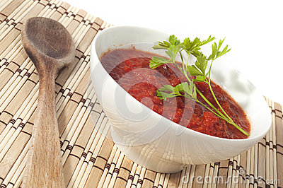 Bowl of tomato sauce on wooden sticks tablecloth
