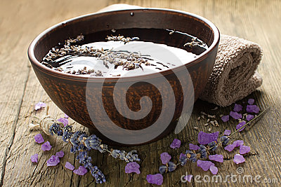 Bowl of water and lavender petals and salt