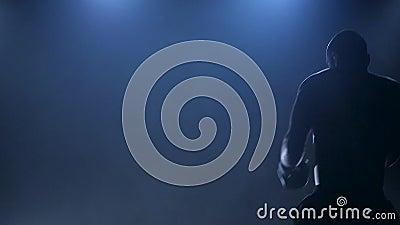 Boxer demonstrates their abilities in sports. Dark studio with smoke Stock Photo