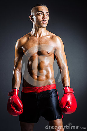 Boxer with red gloves in dark