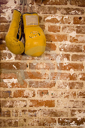 Boxing gloves hanging on brick wall