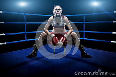 Boxing woman sitting alone in the boxing arena , surrounded by blue lights Stock Photo