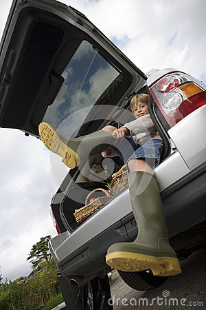 Free Boy (8-10) Putting On Wellington Boots, Sitting In Boot Of Stationary Car, Smiling, Portrait, Low Angle View (tilt) Royalty Free Stock Image - 41711636