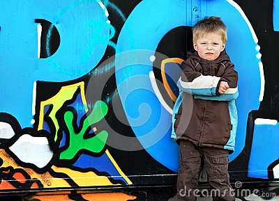 Boy against graffiti wall.