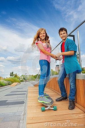 Free Boy And Girl Hold Hands When She Rides Skateboard Royalty Free Stock Images - 46004519