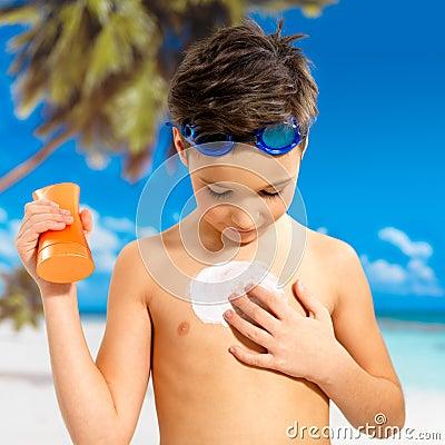 Boy applying sun block cream on the tanned body