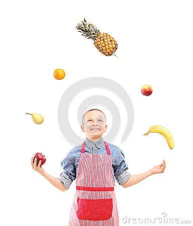 A boy with apron juggling with fruits