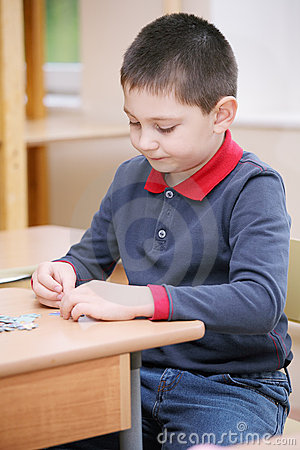 Boy assembling puzzles