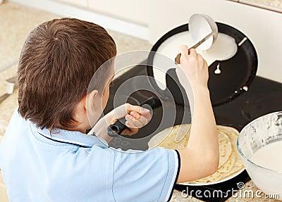 Boy bakes pancakes at home