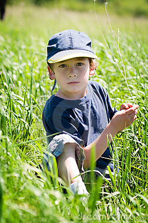 Boy in ball cap sitting in grass