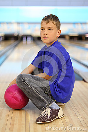 Boy with ball sits on floor in bowling