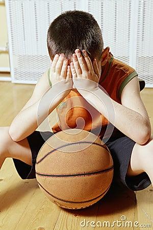 Boy with basketball on floor closeup