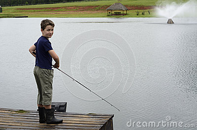 Boy bass fishing on dam or lake pier