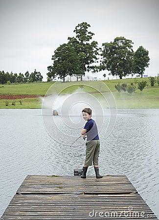 Boy bass fishing on lake pier