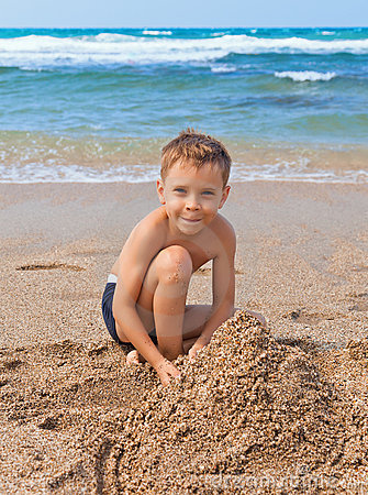 Boy on the beach with sand