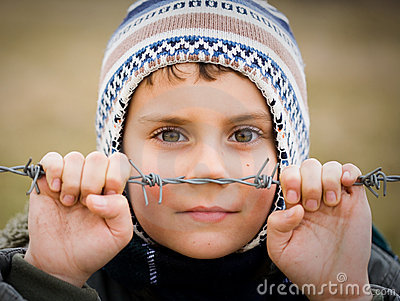 Boy behind barbed wire