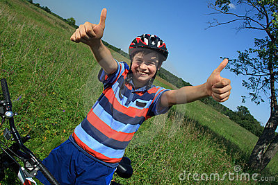 Boy with bicycle giving OK