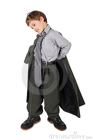 Boy in big man s suit and boots dressing jacket