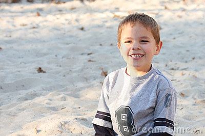 Boy with a big smile in sand