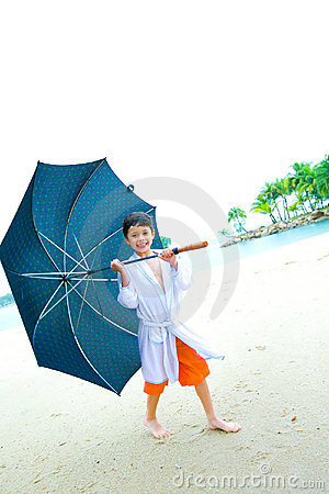 Boy with big umbrella standing at the beach,