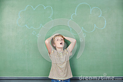 Boy at blackboard with thought