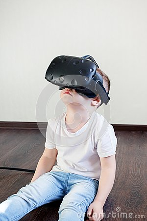 Free Boy Blond 4 Years Old In A White T-shirt And Jeans In A Helmet Of Virtual Reality, Modern Technology, Indigo Children. Royalty Free Stock Images - 119301859