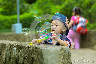 Boy In Blue Fitted Cap Playing Bubbles And Leaning On Grey Concrete Wall At Daytime Free Public Domain Cc0 Image