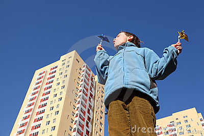 Boy in blue jacket blowing on pinwheels