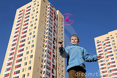 Boy in blue jacket plays with propeller