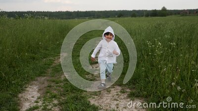 Boy in blue pants and a white jacket in a hood runs along the road stock video