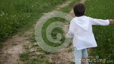 Boy in blue pants and a white jacket in a hood runs along the road stock footage
