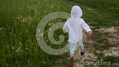 Boy in blue pants and a white jacket in a hood runs along the road stock video footage