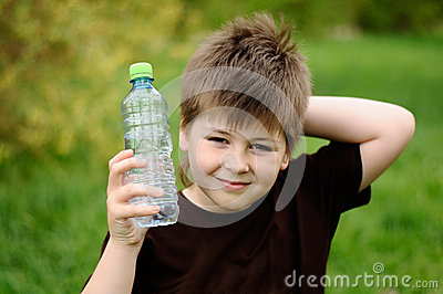 Boy with a bottle of water in nature