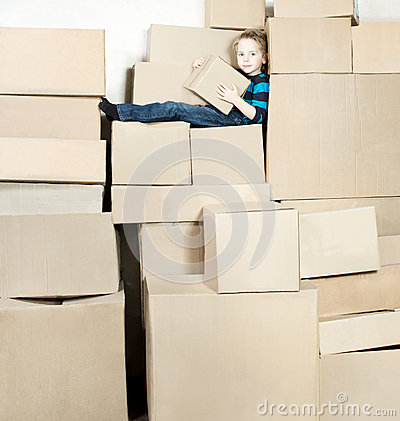 Boy with box sitting on heap boxes