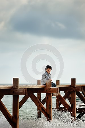 Boy on the bridge at the sea