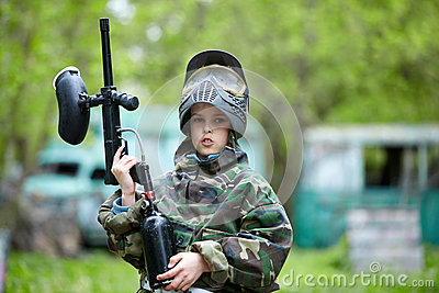 Boy in camouflage holds a paintball gun barrel up