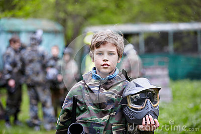 Boy in camouflage holds paintball gun barrel up