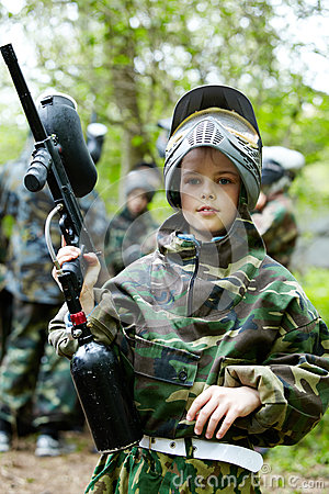 Boy in camouflage suit holds a paintball gun