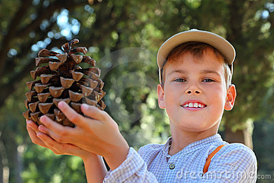 Boy in cap and checkered shirt holding big cone