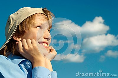 Boy in a cap under a blue sky