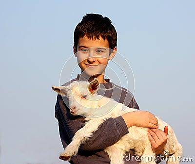 A boy carry a baby goat