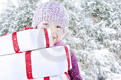 Boy carry christmas gifts on snow background