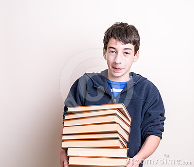 Boy carrying a heavy load of books