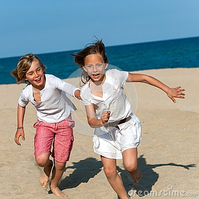 Boy chasing girl on beach.