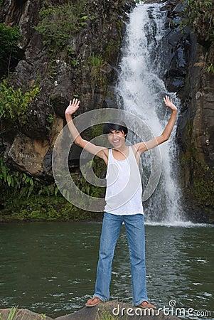 Boy cheering at waterfall