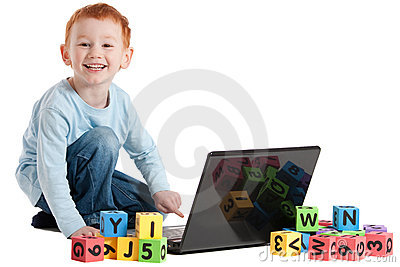 Boy child at school with computer and kids blocks