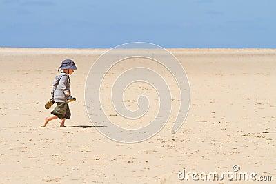 Boy child walking barefoot on sand