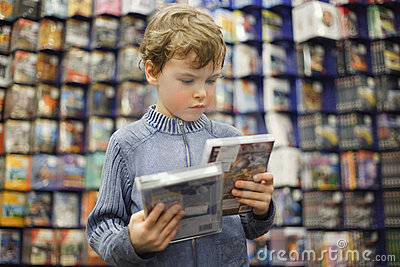 Boy chooses one of two dvd in special store