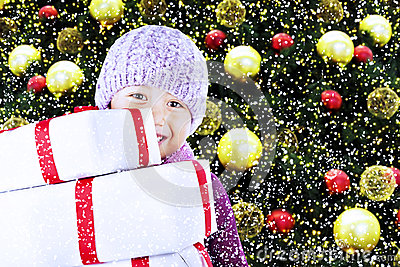 Boy with christmas gifts under tree