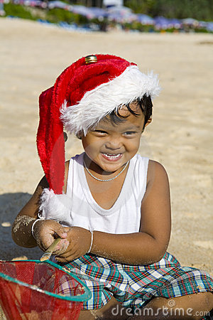 Boy with Christmas hat on beach